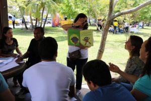 Na foto, Ana Paula Silva, articuladora da Rede de Leitura, está em pé apresentando uma das obras da Coleção Regionais.