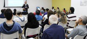 foto do auditório da Fundação Dorina com dezenas de pessoas sentadas. Em segundo plano, de frente para a plateia, está o palestrante Gabriel Perissé. Ele tem pele clara, cabelos grisalhos, barba curta e usa óculos de armação preta.