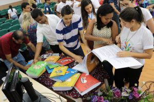 Na foto, várias pessoas reunidas em volta de uma mesa com os livros da coleção Regionais