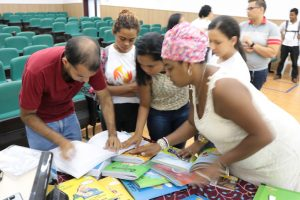 Na imagem, Angelita mostra para um grupo os livros da Coleção Regionais
