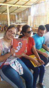 Três adolescentes sentados folheando livros da coleção regionais. EM primeiro plano uma jovem sorrindo exibe o livro Negrinho do Pastoreio.