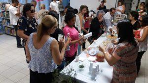 Na foto, mesa repleta de quitutes. Em volta da mesa, pessoas em pé provam as delicias.