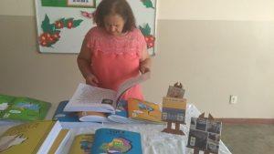 Mulher em pé manuseia os livros da coleção Regionais.