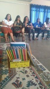 foto em primeiro plano de uma caixa com livros escrito Coleção Regionais. Ao fundo cinco mulheres sentadas olhando para frente.