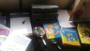 """Descrição de imagem: Foto de uma mesa com dois livros infantis em tinta-braile. O livro no centro da mesa tem o desenho de um menino com boné e o título, em amarelo: """"O grande dia"""". À direita, está o livro """"Cavalinho de Balanço"""", que tem fundo azul e a ilustração de duas crianças em um cavalo de madeira. Na mesa, há ainda uma máquina Braille, duas lupas e uma prancheta com uma folha em branco, em cima da qual há uma reglete e uma punção."""