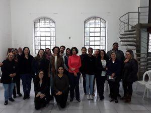 Descrição de imagem: Foto de 18 pessoas em uma sala. Elas estão em pé e sorriem. Ao fundo, estão duas janelas grandes e uma escada em caracol.