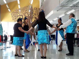 Descrição de imagem: Um grupo de seis pessoas, dois homens e quatro mulheres, está em pé, em roda, e de mãos dadas. As mulheres usam saia azul em tecido brilhante, camisa preta e chapéus pequenos na cabeça. Os homens usam colete no mesmo tom de azul e calça preta. Eles seguram lenços nas cores azul e branco. Ao fundo, está uma grande árvore de madeira, representando um Baobá.