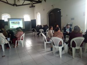 Descrição de imagem: Foto de uma sala retangular com cerca de vinte pessoas. Elas estão divididas em grupos de cinco a seis membros e conversam entre si. Ao fundo, há uma projeção com a imagem do blog da Rede de Leitura Inclusiva.