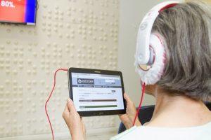 Descrição de imagem: Foto de uma mulher acessando a Dorinateca. Ela está de costas, tem cabelos grisalhos, usa camisa branca e fones de ouvido, e segura um tablet que mostra a página inicial da Dorinateca.
