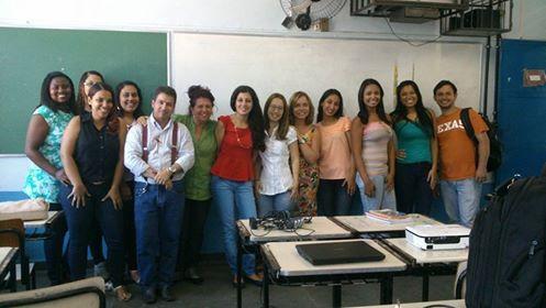 Foto de uma sala de aula,ao fundo lousa verde com grupo de 13 pessoas - estudantes e professores -em pé pousando para foto. A frente do grupo quatro carteiras escolares unidas, acima delas mochila, computador e acessórios e projetor.