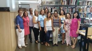 Descrição de imagem: 11 participantes pousam para a foto, estão todos em pé. Ao fundo prateiras com livros, na lateral esquerda um armário, na lateral direita parte de uma mesa de escritório.