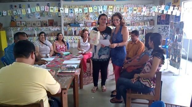 Participantes sentados em circulo em volta de uma mesa retangular cumprida, ao centro há duas mulheres uma delas segura uma folha e a outra uma pequena caixa. Ao fundo prateleiras com muitos livros e varais com livretos coloridos.