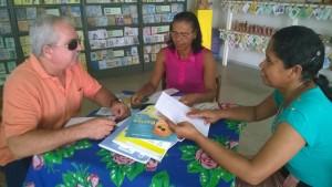 Grupo de três participantes do projeto, sentados ao redor de uma mesa; sendo um homem e duas mulheres. Ao centro da mesa alguns livros, nas mãos dos participantes seguram folhas de papel. Uma das mulheres passa um dedo sobre a folha em branco.