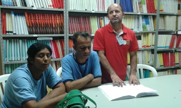 Três pessoas em volta de uma mesa pousam para a foto. Duas delas estão sentadas e um homem está em pé tateando um livro braile aberto sobre a mesa. Ao fundo estantes cheias de livros.