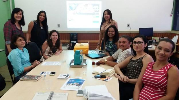 Ao centro mesa de reunião com pessoas ao redor pousando para a foto. São 9 mulheres, algumas sentadas outras em pé. Ao fundo uma projeção de slide na parede de cor branca.