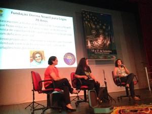 Em um palco três mulheres sentadas em cadeiras vermelhas, a da direita fala ao microfone e as outras a observam. Ao fundo slide da Fundação Dorina projetado e banner do evento.