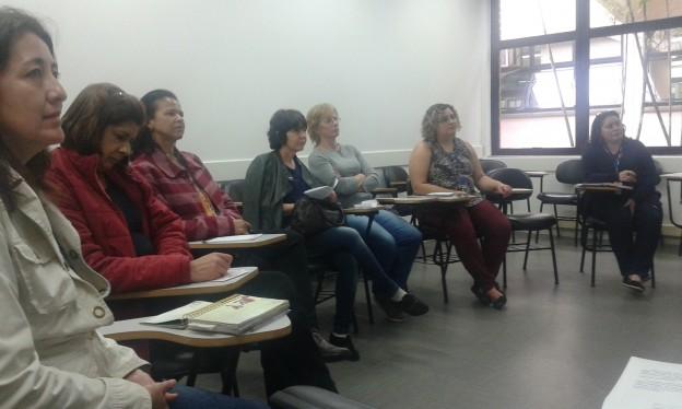 Foto em plano fechado em uma sala de aula com cadeiras dispostas em semicírculo. Sete mulheres sentadas olham para frente.