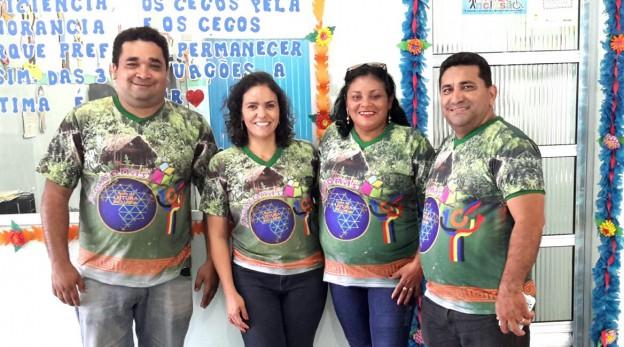 Quatro pessoas pousam para foto sorrindo, os homens nas laterais e as duas mulheres ao centro. Eles vestem camisetas iguais estampadas com a floresta e a logomarca da rede de leitura inclusiva.