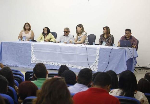 Foto das costas da plateia de um auditório. A frente está a mesa solene com seis pessoas. Uma delas fala ao microfone.