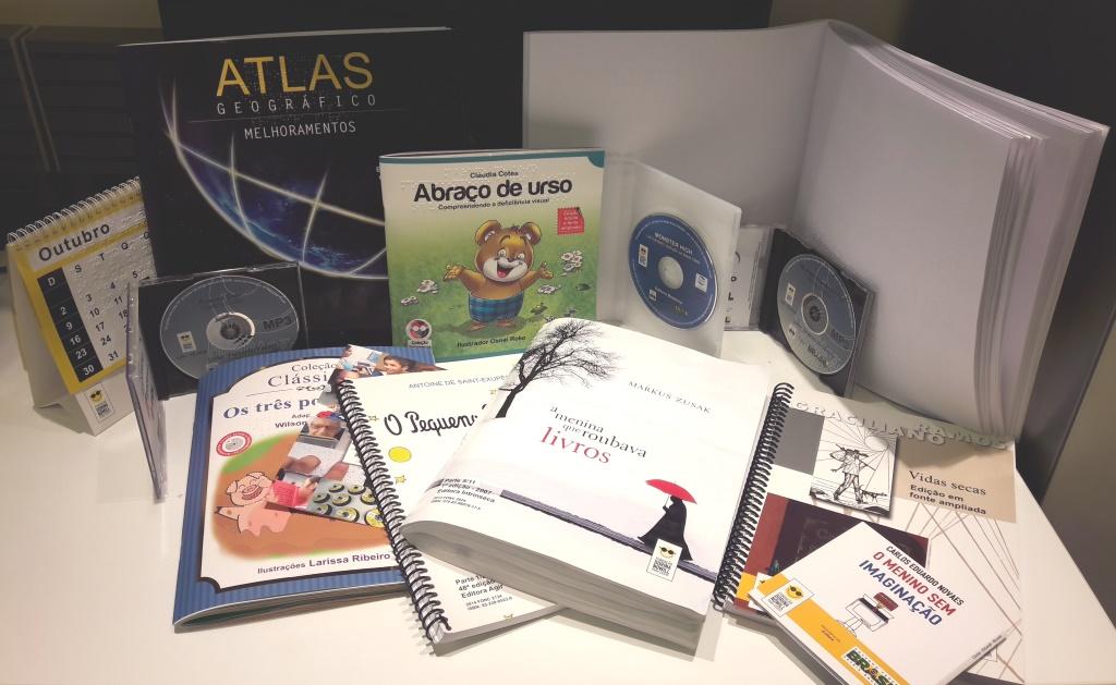 Foto de calendário e de livros acessíveis nos formatos: braile, falado, tinta-braille, fonte ampliada e digital acessível daisy sobre uma mesa.