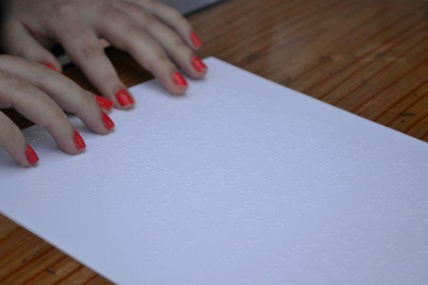 Close de uma folha com texto braile sobre a mesa. Uma mão tateia o final da página. As unhas estão pintadas de esmalte vermelho.