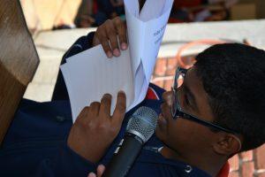 foto de um menino de óculos com folhas escritas próximo ao seu rosto. Ele fala ao microfone.