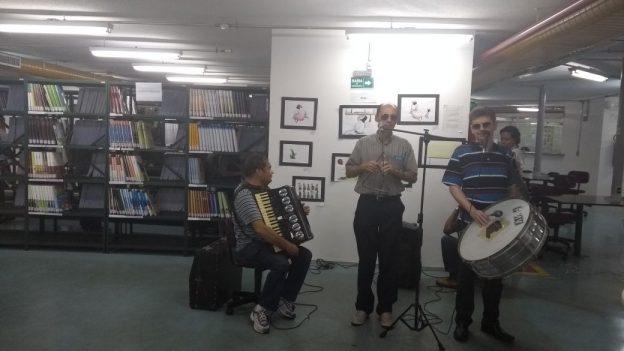 foto três homens tocando sanfona, triângulo e zabumba, o primeiro está sentado. Ao fundo parede com diversos quadros e estantes com livros.