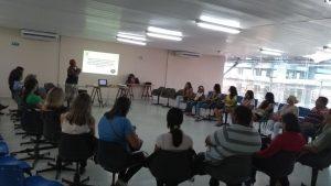 foto tirada do fundo da sala, grupo de 30 pessoas sentadas com cadeiras dispostas em uma grande roda. A frente projeção de slide onde uma pessoa fala ao microfone.