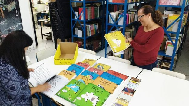 Na foto, duas funcionárias da biblioteca municipal apreciam as obras da Coleção Regionais