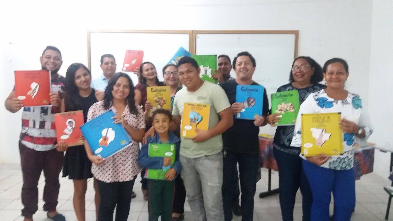 Na foto, um grupo de 12 pessoas em pé, lado-a-lado, sorrindo e segurando livros da Coleção Regionais .