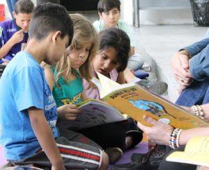 Na foto, três crianças leem a obra Bumba Meu Boi, livro selecionado para a primeira roda de leitura da Coleção Regionais.