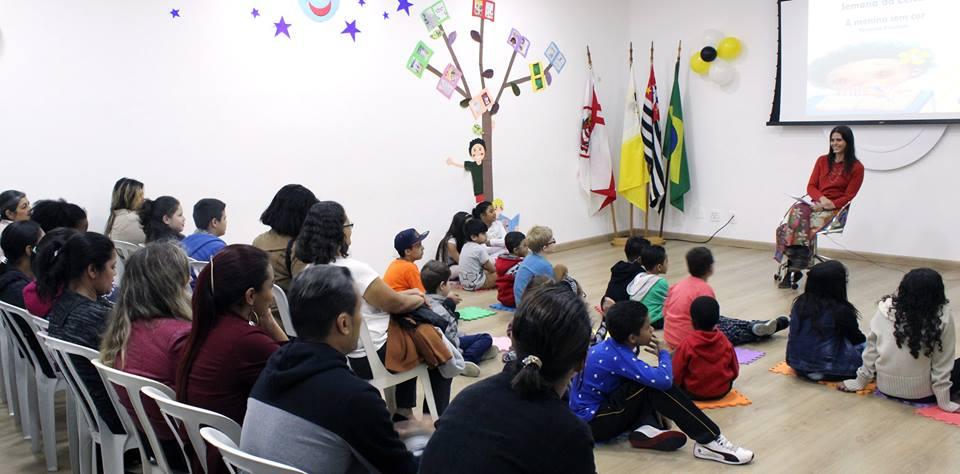 foto de dezenas de adultos sentados em cadeiras e crianças sentadas no chão do auditório da Fundação Dorina. À direita, de frente pra eles e sorrindo, está a escritora Fernanda Emediato.