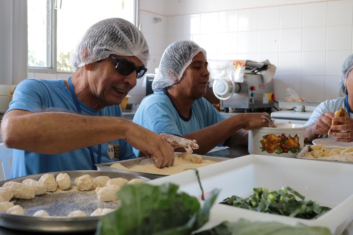 Na foto, um casal, deficiente visual estão sentados à mesa da cozinha preparando virado à paulista, parto típico do sudeste do brasil.