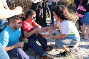 Pessoas em atividade rural. Uma mulher agachada segura um prato de cerâmica em frente a dois jovens sentados no chão. Os jovens estão sentindo a textura das plantas do local e do material dentro do prato.