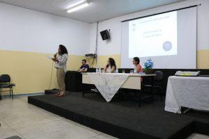 Na imagem, a articuladora Perla Assunção, fala no palco sobre leitura inclusiva
