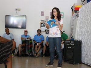 Na foto, a atriz Mariana da Cruz Martins Bressan está em pé lendo o livro Cuca, da Coleção Regionais