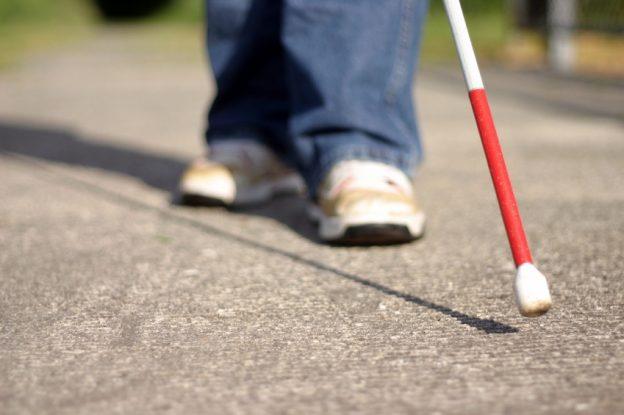 Imagem mostra apenas os pés de um deficiente visual andando pela rua com sua bengala.