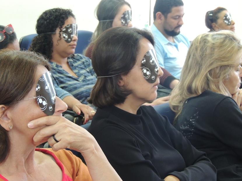 Na imagem, pessoas sentadas com os olhos vendados.