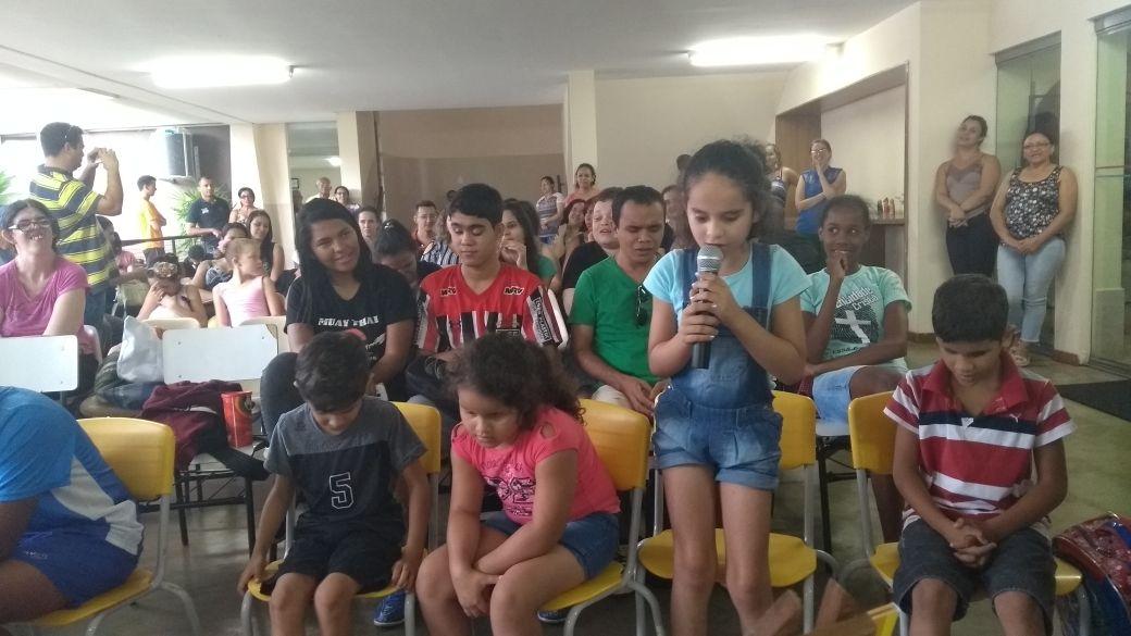 Grupo de crianças sentadas e uma menina de pé com o microfone na mão