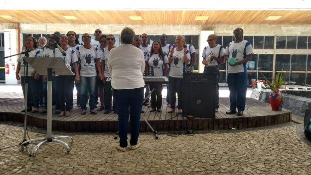 Grupo de 18 pessoas cantam e tocam para o público.