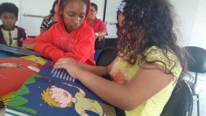 Crianças sentadas conhecem as obras da Coleção