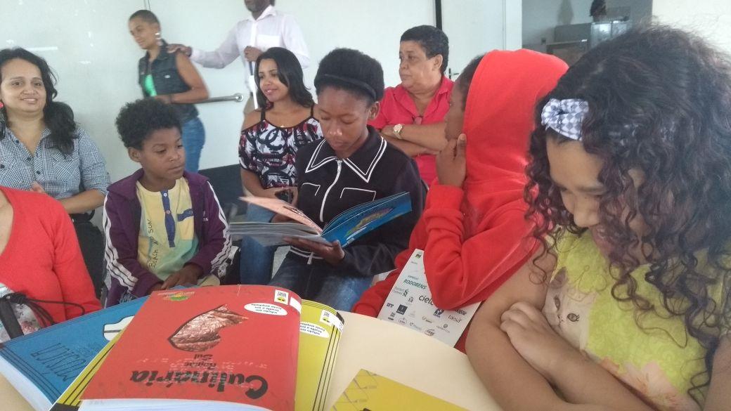 Crianças manuseiam os livros da coleção Regionais