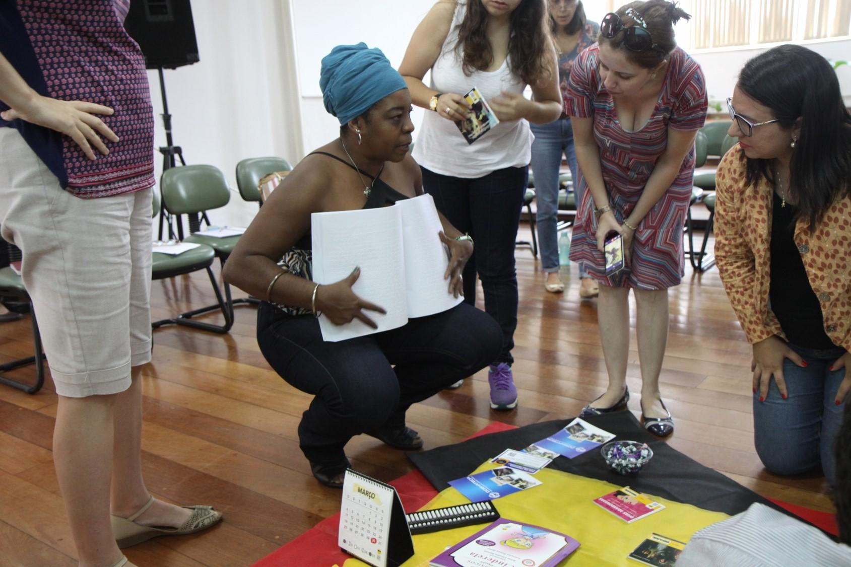 Descrição de imagem: Angelita apresenta um livro em braile à quatro participantes da oficina, que estão em pé em uma roda. No chão, há uma toalha preta com diversos livros dispostos e o calendário acessível 2018 da Fundação Dorina.