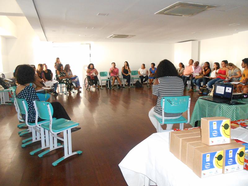 Descrição de imagem: Cerca de trinta pessoas sentadas em roda em uma sala ampla. À frente uma mesa com kits de audiolivros do projeto Leitura Digital Acessível.