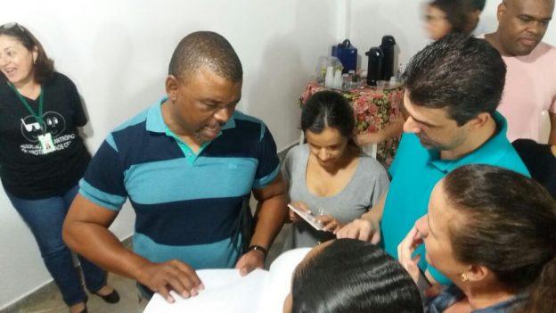 Descrição de imagem: Foto de três participantes da oficina, um homem e duas mulheres, sentados em volta de uma mesa redonda acessando o Daisy no computador. Nayara está à esquerda. Ela é negra, tem cabelo liso e preto na altura dos ombros. Usa uma camisa branca, blayzer vermelho e calça jeans.