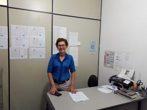 Descrição de imagem: Foto de Maria Helena, fundadora da Para-DV, em uma sala. Ela está em pé, atrás de uma mesa com artigos de escritório. Maria Helena é branca, tem cabelos curtos e castanhos. Usa óculos de grau e brincos pequenos, camisa azul e calça jeans.