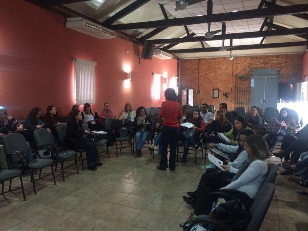 Descrição de imagem: Foto de uma sala com cerca de 20 pessoas sentadas em roda. Célia está em pé, no centro da roda e conversa com a turma. A sala tem paredes vermelhas e pé direito alto.