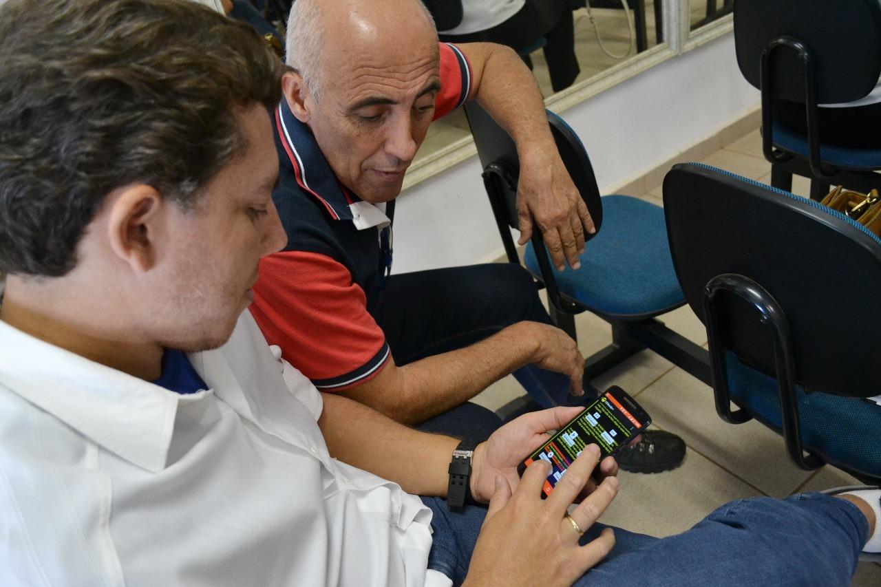 Descrição de imagem: Dois homens utilizam o DDReader em um aparelho celular. Os dois estão sentados um ao lado do outro.