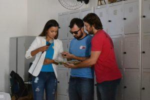 Descrição de imagem: Milena está ao lado de dois rapazes. Eles estão em pé. Milena segura um microfone, enquanto o vocalista da banda A Visão do Coração aponta um celular para um livro. O terceiro rapaz segura o livro abaixo do celular. Ao fundo, estão diversos armários de parede.