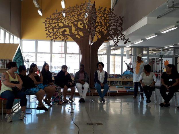 Descrição de imagem: Na foto, 10 participantes do evento estão sentados em roda na Biblioteca Maria Firmina dos Reis. Uma delas fala ao microfone. A sala é espaçosa e cercada por janelas de vidro. Ao fundo, há uma grande árvore de madeira representando um Baobá, com almofadas coloridas em volta.